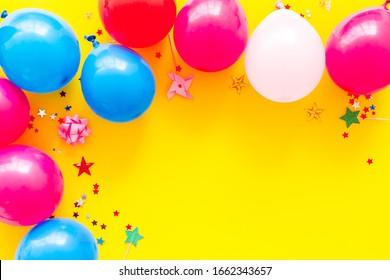 Parteikonzept. Farbige Ballons und Konfetti auf gelbem Hintergrund, Kopienraum im oberen Rahmen