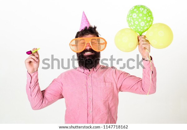 Party concept. Hipster in giant sunglasses celebrating birthday. Man with beard and mustache on happy face holds air balloons, white background. Guy in party hat with party horn celebrates.