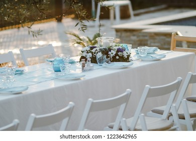 Party decoration Festive table with plates, glasses and blue textiles outdoor