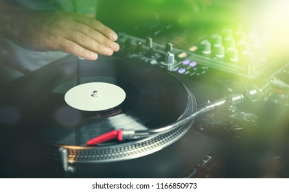 Party dj plays music in bright stage lights in night club.Hands of musician and vintage turnables player.Disc jockey mix musical tracks with old analog audio equipment.Turn table and mixer on stage