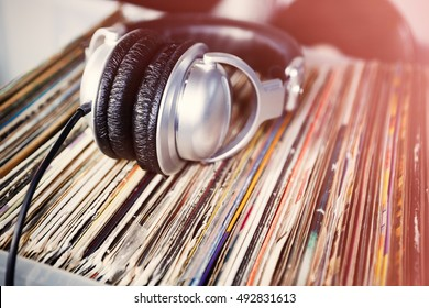 Party Dj turntable & vinyl records collection.Retro hipster sound system.Listen to record disc in headphones.Vintage audio setup,studio equipment.Head phones for professional hip hop disc jockey