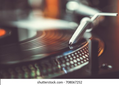 Party dj turntables.Vinyl records player needle cartridge on disc with music in night club.Disc jockey plays musical tracks at professional turn table device.Hi-fi audio equipment on stage
