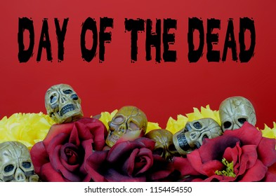 Party favor skulls laying among silk red roses and yellow paper marigolds with a red background. Day of the Dead text added for Mexicon holiday in October