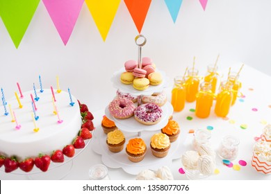 party and festive concept - birthday cake with candles and strawberries, drinks and food on table