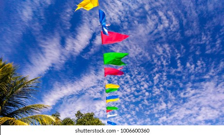 Party flags in Brazil of a cultural party of São João, with a beautiful and cloudy sky.