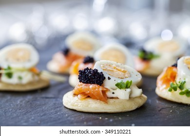 Party food, blinis with salmon, quail egg and caviar