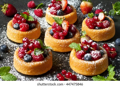 Party food: mini cakes with berry mousse, caramel and fresh berries