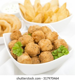 Party Food - Popcorn chicken, potato wedges, onion rings and breaded mushrooms on a white background.