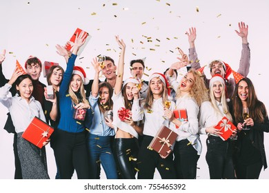 Party with friends. Group of cheerful young people in Santa hats with gift boxes showered with confetti. Celebration concept.
