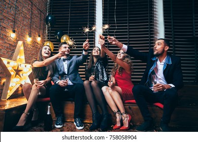 Party with friends. Happy young people carrying sparklers and having fun. New year, Birthday, Holiday Event concept