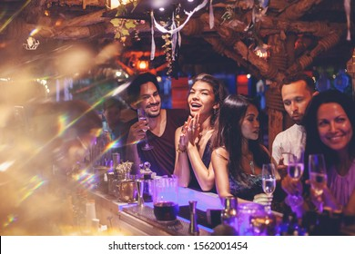 A party of friends in a nightclub at the bar, glamorous young people relax with alcohol.
