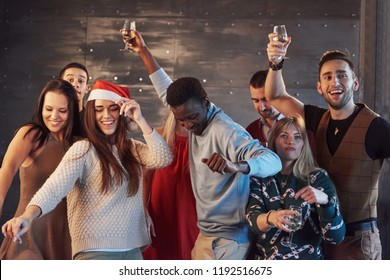Party with friends. They love Christmas. Group of cheerful young people carrying sparklers and champagne flutes dancing in new year party and looking happy. Concepts about togetherness lifestyle.