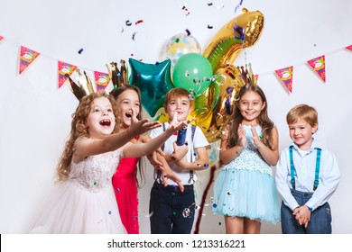 Party fun. Group of beautiful kids throwing colorful confetti and looking happy on birthday party