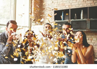 Party fun. Group of beautiful young people throwing colorful confetti and looking happy