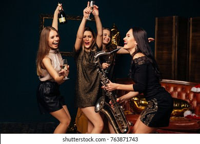 Party fun. Group of beautiful young happy women dancing, drinking champagne and playing on saxophone at party