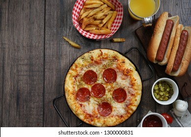 Party game day food Homemade Pizza hot dogs fries juice and dips - Super bowl food concept overhead view