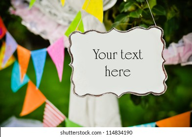 Party garland and empty board with space for text against green trees