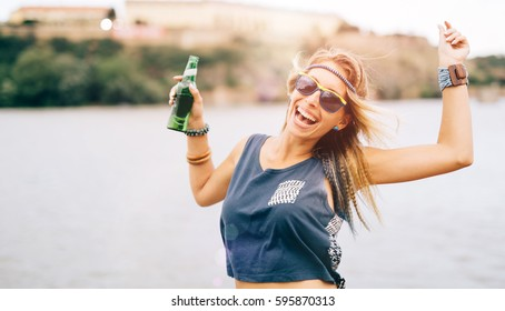 Party girl at summer festival holding drink and having fun