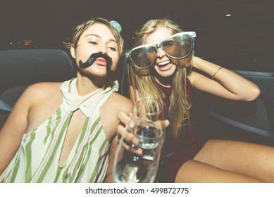Party girls celebrate in Hollywood drinking champagne on a convertible car