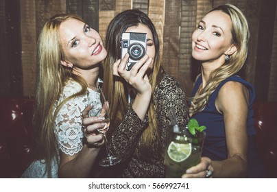 Party girls in a restaurant celebrating with drinks and champagne