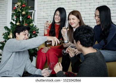 Party of group young Asian with pour wine for drink at home in celebrate Christmas festival. Celebration of new year at house. Merry Christmas and happy holidays of gang teen thai.