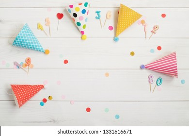 Party hat and candles on wooden background.