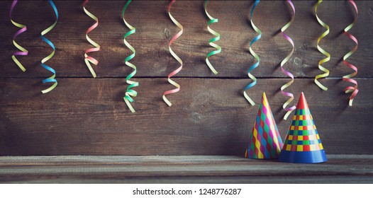 party hat ,streamers on wooden board with copy space
