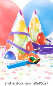 Party hats, horns or whistles, confettis and balloons on white background.