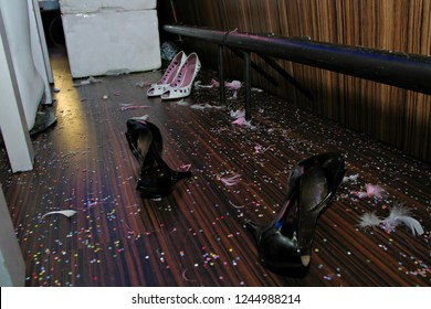 Party High Heels Shoes on Confetti Covered Floor - after party. Messy still life.