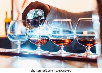 Party and holiday celebration concept. Empty glasses for cognac on the bar counter. cognac bottling process. with the hand view