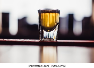 Party and holiday celebration concept. Image of multicolored liqueurs in shots on a wooden stand behind the bar. one shot close up view