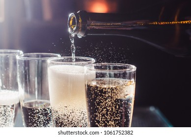 Party and holiday celebration concept. Many glasses of champagne on the table in the restaurant. The process of bottling champagne in glasses. close up view