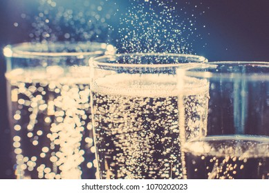 Party and holiday celebration concept. Many glasses of champagne on the table in the restaurant. Toned image. The process of bottling champagne in glasses. bubbles view close up view