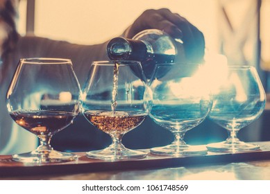 Party and holiday celebration concept. Toned image. Cognac filled glasses on the bar counter. cognac bottling process.