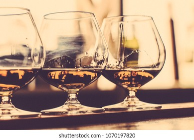 Party and holiday celebration concept. Toned image. Cognac filled glasses on the bar counter. cognac bottling process. from the front view close