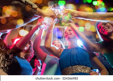 party, holidays, celebration, nightlife and people concept - happy women with clincing glasses of non-alcoholic champagne in club
