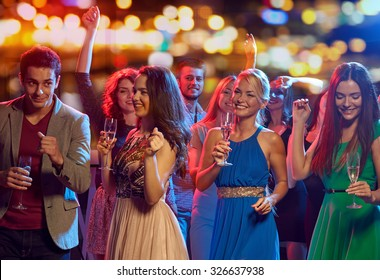 party, holidays, celebration, nightlife and people concept - happy friends with glasses of non-alcoholic champagne dancing at disco in nightclub