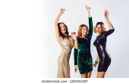 Party and holidays concept. Three glamour women in luxury glitter sequins dress  having fun. Hollywood make up, wavy hairstyle. White background.