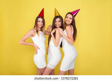 Party and holidays concept. Three glamour women in luxury glitter sequins dress dancing and having fun wearing holiday caps