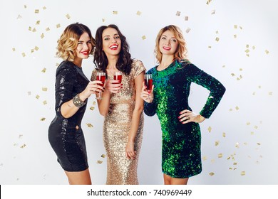 Party and holidays concept. Three glamour women in luxury glitter sequins dress drinking cocktails  and having fun. Hollywood make up, wavy hairstyle. White background.