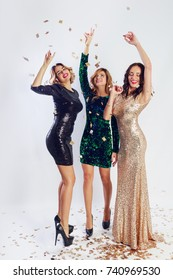 Party and holidays concept. Three glamour women in luxury glitter sequins dress dancing and having fun. Hollywood make up, wavy hairstyle. White background. Full height.