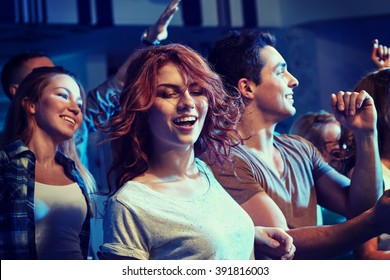 party, holidays, nightlife and people concept - happy friends dancing at night club