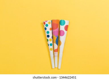 Party horn noise makers on a yellow paper background