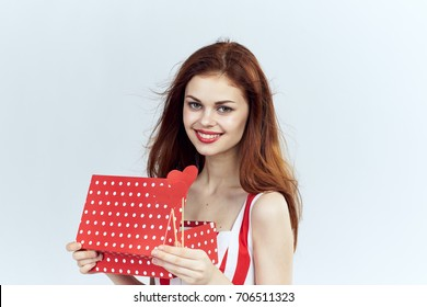 Party, joyful woman holding a gift box and accessory on a stick on a light background, holiday