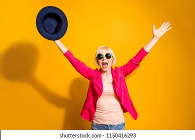 Party mood! Portrait of old woman stretching her arms upwards waving her hat celebrating the victory isolated on vivid yellow background