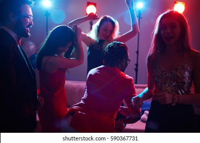 Party in night club: group of pretty woman in trendy dresses and stylish men dancing with smiles on their faces and enjoying each others company