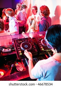 Party in a nightclub viewed from the DJ booth