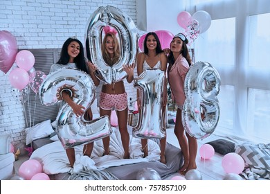 Party is on! Four attractive young smiling women in pajamas holding balloons while standing in the bedroom at home