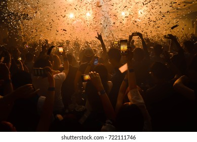 Party people concept. Crowd happy and joyful in club.Celebration party festival happyness. Blurry night club.DJ show concert playing  music EDM on stage  Bangkok Thailand.