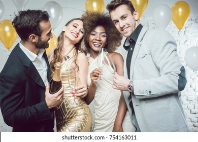 Party people with drinks celebrating new year or a birthday party together in a club